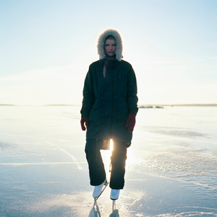 Sweden, Uppland, Varmdo, Bjorno, Mid adult woman in ice skates standing on frozen lakeの写真素材 [FYI02201218]