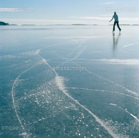 Sweden, Stockholm Archipelago, Uppland, Varmdo, Bjorno, Mid adult woman ice skating on frozen lakeの写真素材 [FYI02201266]