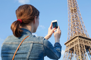 France, Ile-de-France, Paris, Rear view of woman taking picture of Eiffel Towerの写真素材 [FYI02201324]