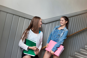 Two girls (14-15) standing on staircase, smilingの写真素材 [FYI02201401]