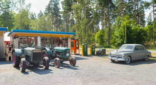 Sweden, Smaland, Visingso, Old fashioned car and tractors in gas stationの写真素材 [FYI02201446]