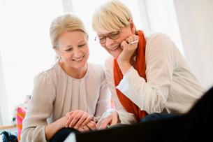 Two smiling women looking downの写真素材 [FYI02201448]
