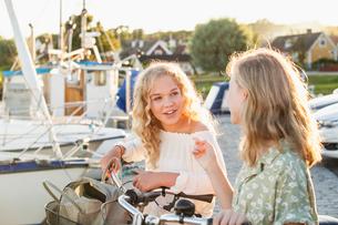 Sweden, Blekinge, Hallevik, Two teenage girls(14-15, 16-17) with bicycles talking at marina bayの写真素材 [FYI02201490]