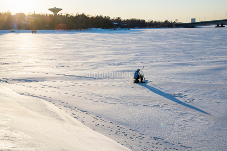 Finland, Helsinki, Drumso, Man making ice holeの写真素材 [FYI02201509]