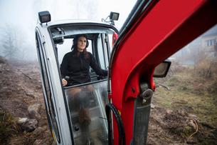 Sweden, Uppland, Nacka, Woman driving bulldozerの写真素材 [FYI02201516]