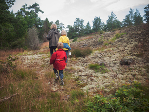 Sweden, Smaland, Horn, Mother with two children (4-5, 8-9) walking on moorlandの写真素材 [FYI02201566]