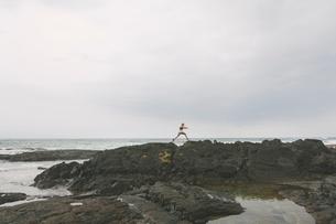 USA, Hawaii, Big Island, Man jumping over cleft in rock formation on seashoreの写真素材 [FYI02201630]