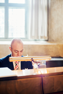Sweden, Gastrikland, Sandviken, Man wearing suit working at counterの写真素材 [FYI02201644]
