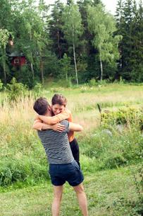 Sweden, Uppland, Danderyd, Hugging couple with forest in backgroundの写真素材 [FYI02201648]
