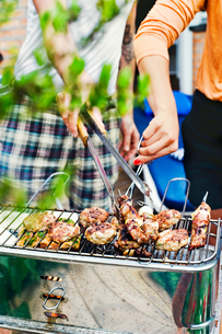 Sweden, Uppland, Danderyd, Couple grilling meat on barbecueの写真素材 [FYI02201697]