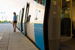 Sweden, Stockholm, Fruangen, Teenage girl (16-17) walking along train at railroad station platformの写真素材 [FYI02201734]