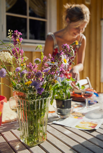 Sweden, Oland, Bouquet of wildflowers with woman in backgroundの写真素材 [FYI02201745]