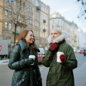 Sweden, Stockholm, Two women holding disposable coffee cupsの写真素材 [FYI02201851]