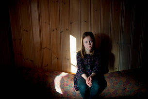 Girl (12-13) sitting against wooden wallの写真素材 [FYI02201855]