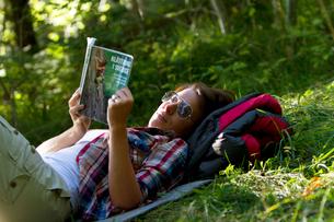 Sweden, Ostergotland, Agelsjon, Female hiker lying on grass and reading guidebookの写真素材 [FYI02201867]