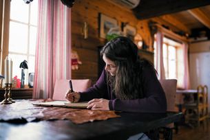 Sweden, Young woman sitting at table and writing in dairyの写真素材 [FYI02201884]