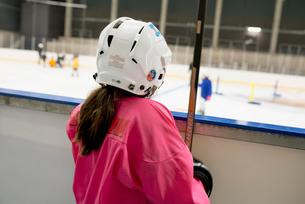 Sweden, Girl (6-7) in ice hockey uniform standing by railingの写真素材 [FYI02201903]