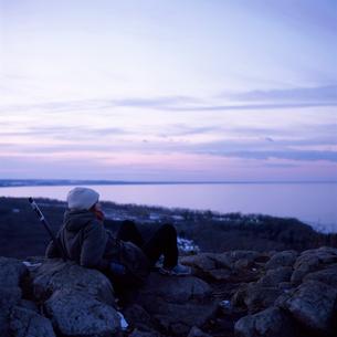Sweden, Skane, Stenshuvud, Woman sitting on stones and watching seaの写真素材 [FYI02201930]