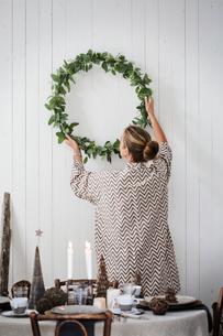 Sweden, Woman hanging Christmas wreath on wallの写真素材 [FYI02201981]