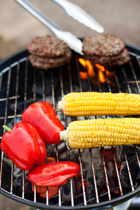 Sweden, Hamburgers, corn and bell peppers on barbecueの写真素材 [FYI02202031]