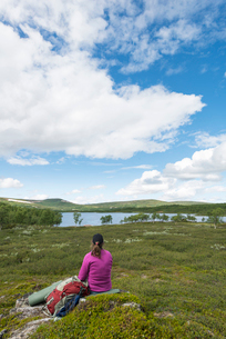 Sweden, Harjedalen, Ojon, Woman with backpack sitting on rock and looking at lakeの写真素材 [FYI02202032]