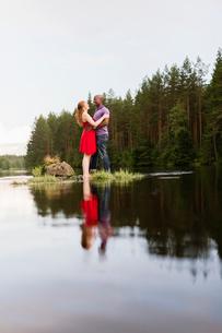 Sweden, Vastmanland, Bergslagen, Svartalven, Mid adult couple embracingの写真素材 [FYI02202052]