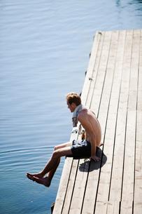 Sweden, Smaland, Loftahammar, Young man sitting on wooden jetty by lakeの写真素材 [FYI02202060]