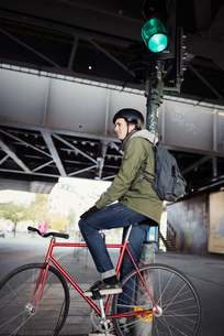 Sweden, Sodermanland, Stockholm, Sodermalm, Slussen, Mid adult man sitting on bicycleの写真素材 [FYI02202061]