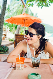 Thailand, Koh Tao, Smiling woman wearing sunglasses sitting with drink in cafeの写真素材 [FYI02202098]