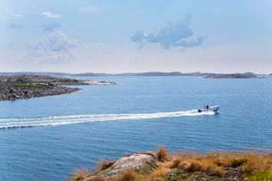 Sweden, Swedish West Coast, Bohuslan, Kyrkesund, Tarneskar, People in boat travelling by coastlineの写真素材 [FYI02202126]