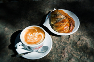Sweden, Stockholm, Sweet bun and cappuccino on tableの写真素材 [FYI02202143]