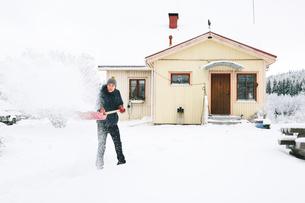 Finland, Jyvaskyla, Saakoski, Man shoveling snow in front of houseの写真素材 [FYI02202221]