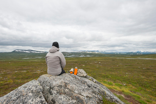 Sweden, Harjedalen, Flatruet, Woman with insulated drink container sitting on rock and looking at moの写真素材 [FYI02202291]