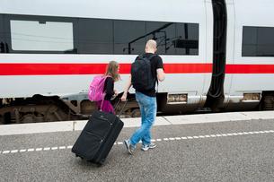 Denmark, Copenhagen, Father and daughter (6-7) walking along railroad station platformの写真素材 [FYI02202351]