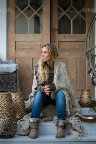 Sweden, Blonde woman wrapped in plaid sitting on house porchの写真素材 [FYI02202394]
