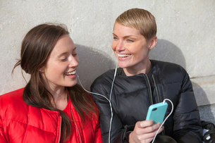 Sweden, Stockholm, Ostermalm, Two women listening to musicの写真素材 [FYI02202399]