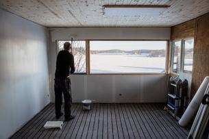 Sweden, Uppland, Stockholm archipelago, Rindo, Man painting wallの写真素材 [FYI02202415]