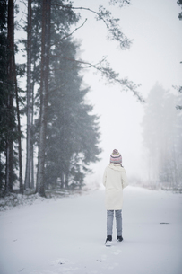 Sweden, Vastmanland, Bergslagen, Girl (8-9) in winter forestの写真素材 [FYI02202428]