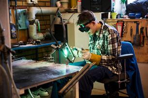 Sweden, Young man welding metalの写真素材 [FYI02202470]