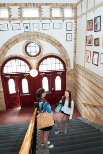 Two girls (14-15) standing on staircase, talkingの写真素材 [FYI02202480]