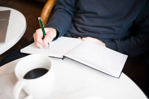 Sweden, Young man writing in note pad in cafeの写真素材 [FYI02202488]