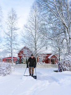 Finland, Pohjanmaa, Pietarsaari, Kruunupyy, Man cleaning yard with snow pusherの写真素材 [FYI02202499]