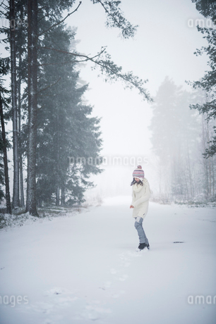 Sweden, Vastmanland, Bergslagen, Girl (8-9) in winter forestの写真素材 [FYI02202509]