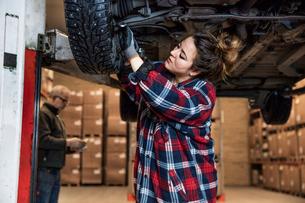 Sweden, Female mechanic adjusting wheelの写真素材 [FYI02202526]