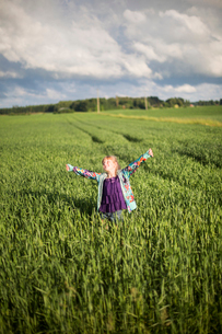 Sweden, Medelpad, Girl (8-9) standing in agricultural field with arms outstretchedの写真素材 [FYI02202546]