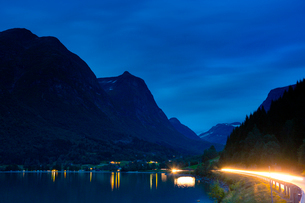 Norway, Sogn og Fjordane, Stryn, Road and light trails on side of lake in mountain valley with refleの写真素材 [FYI02202570]