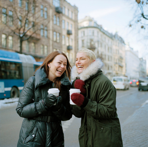 Sweden, Stockholm, Two women holding disposable coffee cups laughingの写真素材 [FYI02202573]