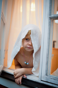 Sweden, Uppland, Moja, Shirtless girl (6-7) leaning against windowの写真素材 [FYI02202596]
