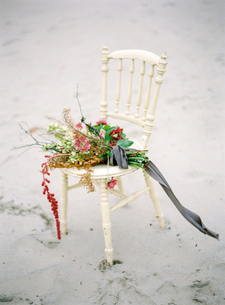 Sweden, Bouquet of flowers on old-fashioned chair on sandy beachの写真素材 [FYI02202609]