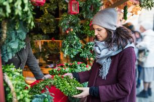 Sweden, Stockholm, Gamla Stan, Woman choosing christmas wreath at marketの写真素材 [FYI02202628]